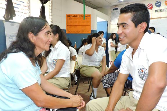 En primer plano una madre conversando con su hijo en un salón de clases  con alumnado y sus familias