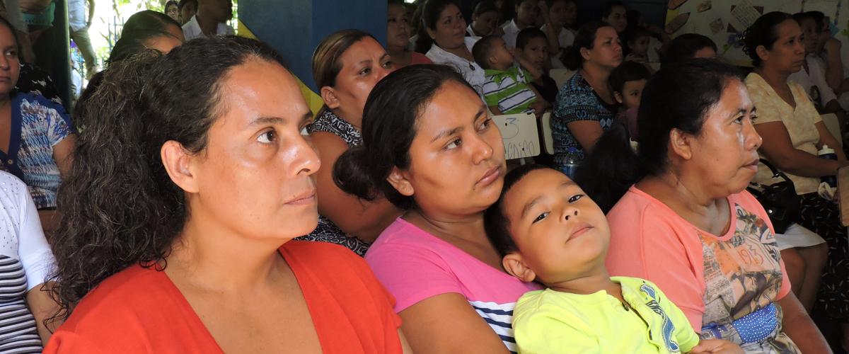 Fotografía de un grupo de personas en una reunión, en primer plano una mujer con un niño en brazos