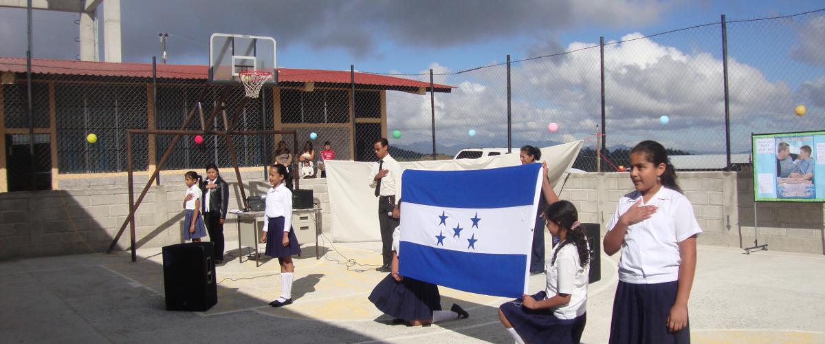 Foto niños haciendo honores a la bandera