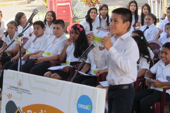 Grupo de niñas, niños y jóvenes con uniforme azul y blanco participando en concurso de deletreo