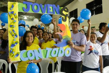 Un grupo de jóvenes con un cartel que dice Jóvenes con todo