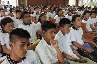 Grupo masivo de jóvenes sentados en la capilla de Centro Monseñor Romero