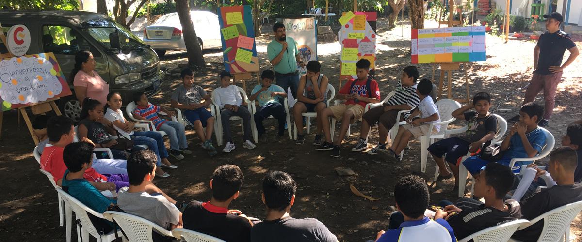 Un grupo de niñas, niños y jóvenes en circulo durante una charla
