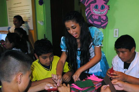 Personaje de Alicia en el país de las maravillas junto a niños en una mesa