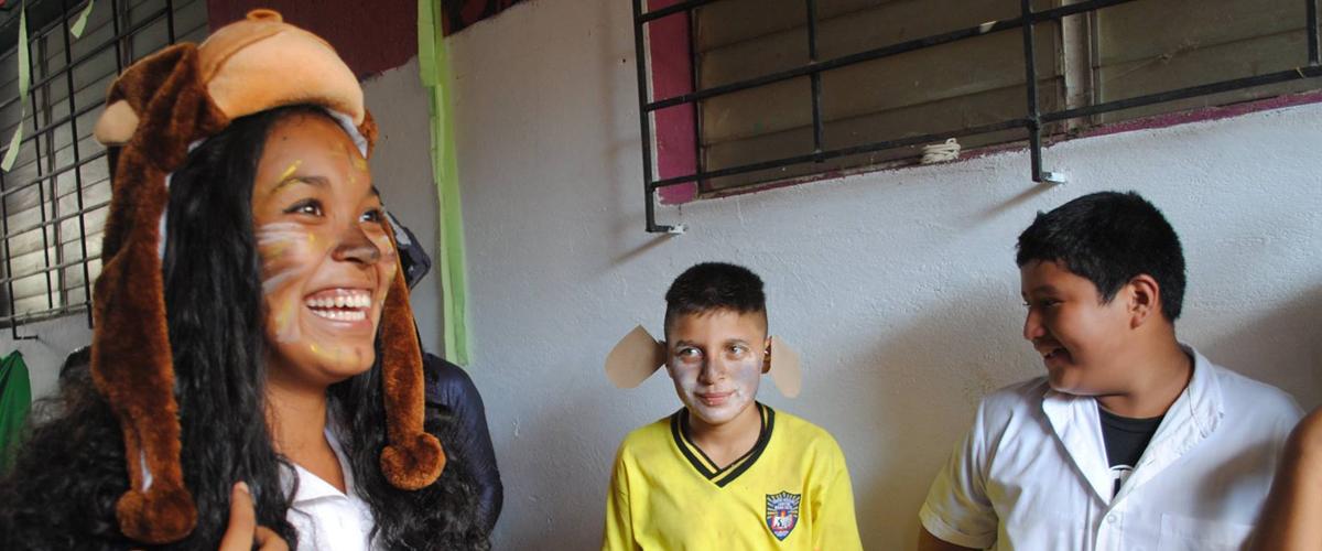 Niña con el rostro pintado con bigotes y sobre su cabeza la figura de un mono en un gorro