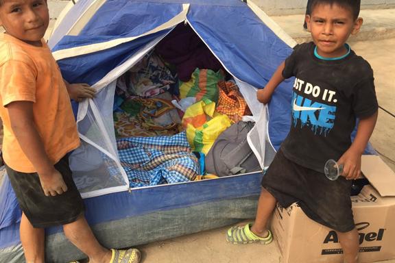 Niños con los enseres que han quedado tras las lluvias Perú - Huachipa