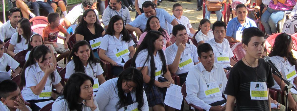 Un jóven frente a un micrófono participa en el certamen de deletreo, tras él sentados jóvenes, niñas y niños participantes