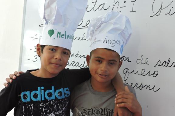 Dos niños con sombreros de cocinero abrazados a los hombros