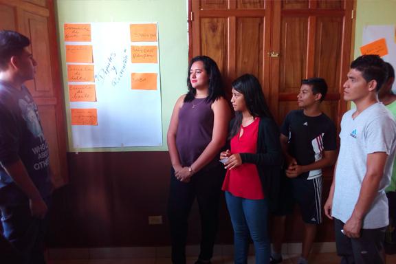 Grupo de jóvenes frente a un cartel con propuestas de actividades para la juventud