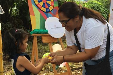 Una joven entrega un premio en las manos a una niña