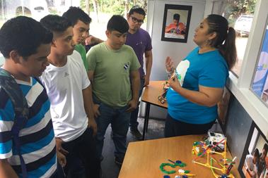 Un grupo de jóvenes escuchan a docente de robótica